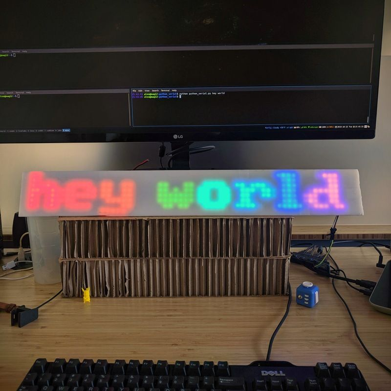 The words 'hey world' glow on a long acrylic rectangle under a computer monitor.