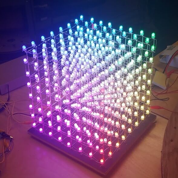 Several hundred glowing LEDs form a one foot tall cube on a table.
